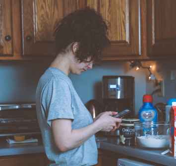 woman holding smartphone in the kitchen